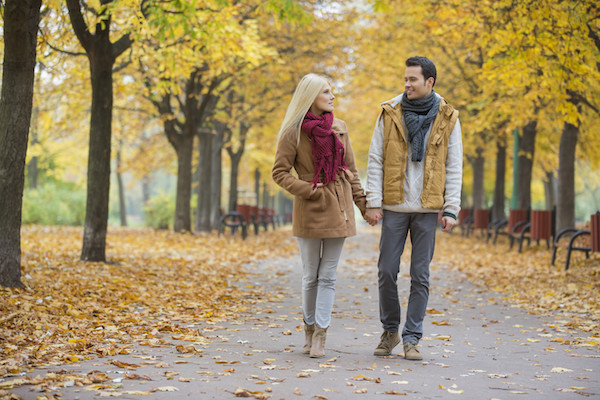 Couple holding hands while walking in park during autumn